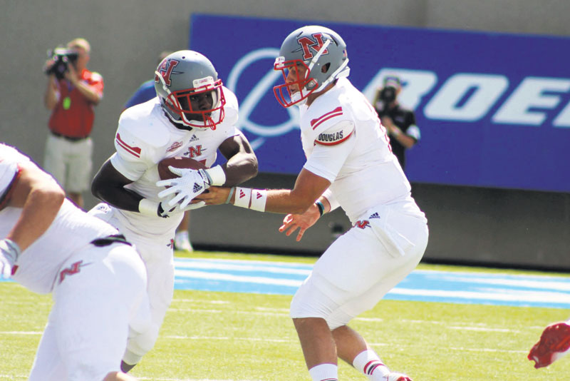 Nicholls quarterback Beaux Hebert (right) hands off to runningback Tobias Harris during Saturday's game against Air Force in Colorado Springs, Co.