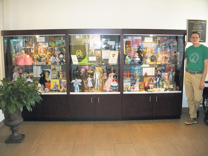 David Dicket, senior music major from Thibodaux, poses with one of the display cases of his Wizard of Oz collection in the Thibodaux Branch Library.