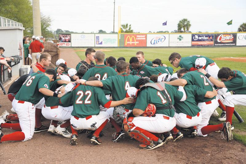 The+baseball+team+praying+together+before+their+home+game+against+Lamar+on+March+17th.+