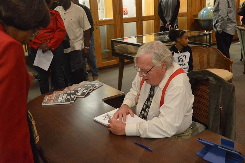 Author John DeSantis signs a book during his