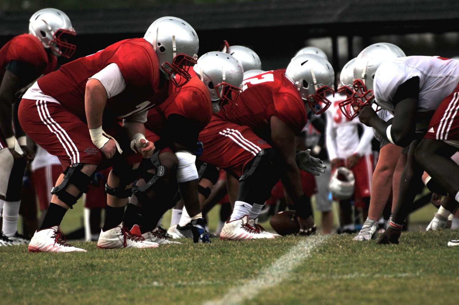 Offensive+and+defensive+linemen+get+into+formation+on+the+line+of+scrimmage+at+afternoon+practice+on+Tuesday%2C+September+1.