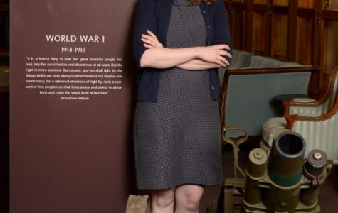 Helen Thomas, assitant archivist, stands next to World War I exhibit in Ellender Memorial Library.