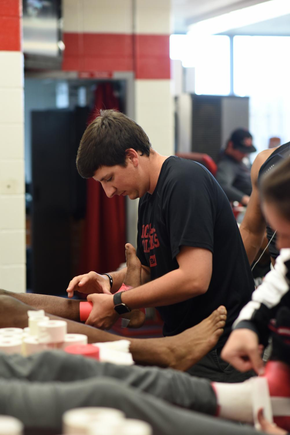 Evan Dauterive, head athletic trainer, wraps a Colonel football player's ankle before practice on Wednesday, March 14.